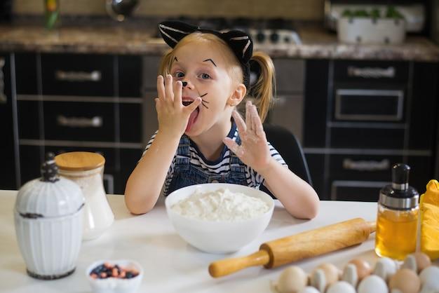 Szczęśliwa dziewczynka w kostiumie kociaka przygotowuje ciasteczka na halloween lub przyjęcie urodzinowe