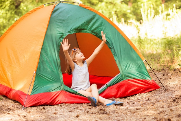 Szczęśliwa dziewczynka w namiocie obozowym cieszyć się leśnymi wakacjami z rękami do góry