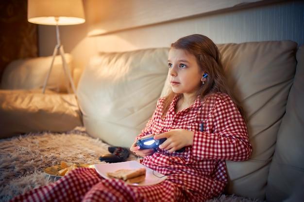 Szczęśliwa dziewczynka w piżamach siedzi na kanapie, je pizzę i grając w gry wideo z joystickiem w domu