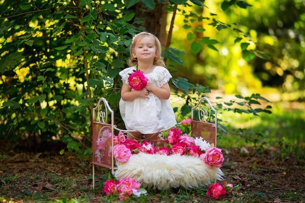 Szczęśliwa dziewczynka w stroju księżniczki retro w łóżku z różowe kwiaty na zewnątrz w lecie