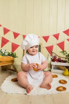 Szczęśliwa dziewczynka w stroju szefa kuchni trzyma bajgla i uśmiecha się