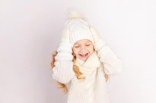 Szczęśliwa dziewczynka w swetrze i kapeluszu trzymająca głowę na białym tle na białym tle, miejsce na tekst