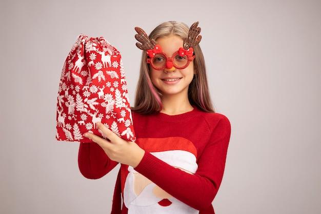 Szczęśliwa dziewczynka w świątecznym swetrze w zabawnych okularach imprezowych, trzymająca czerwoną torbę świętego mikołaja z prezentami, patrząc na kamerę, uśmiechając się radośnie stojąc na białym tle