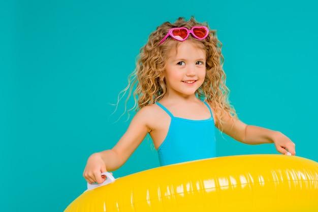 Szczęśliwa dziewczynka w swimsuit z okręgiem odizolowywającym na błękitnym tle