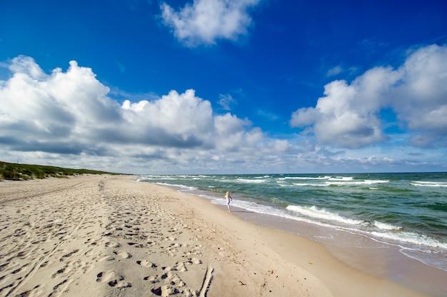 Szczęśliwa dziewczynka w ubraniach na plaży morza bałtyckiego na mierzei kurońskiej na litwie.
