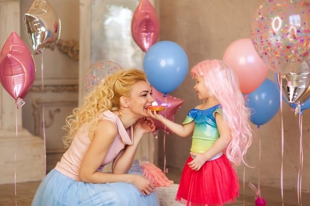 Szczęśliwa dziewczynka w wieku 3-4 lat w różowej peruce karmi pysznego pączka swojej matce, urodziny dziecka