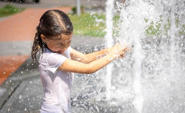 Szczęśliwa dziewczynka wśród pluskającej wody miejskiej fontanny bawi się i ucieka przed upałem.