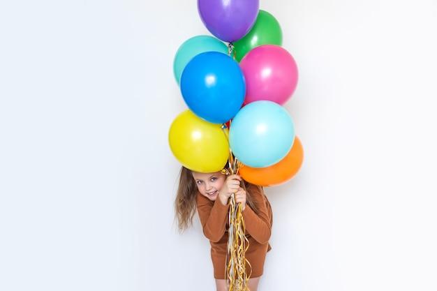 Szczęśliwa dziewczynka wygląda zza pęku balonów, trzymając kolorowe kulki i śmiejąc się wesoło. skopiuj miejsce na tekst