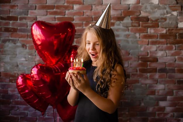 Szczęśliwa dziewczynka wypowiada życzenie i zdmuchuje świeczki na torcie
