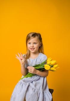 Szczęśliwa dziewczynka z bukietem żółtych tulipanów i pokazuje cztery palce na żółto