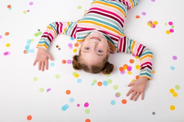 Szczęśliwa dziewczynka z confetti na białym tle