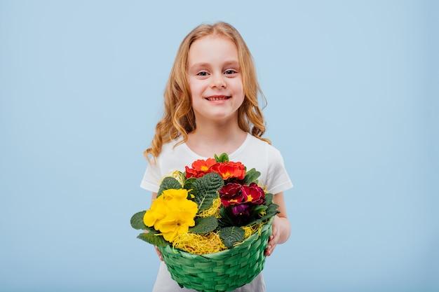 Szczęśliwa dziewczynka z koszem kwiatów w ręku, ubrana w białą koszulkę, na niebieskim tle