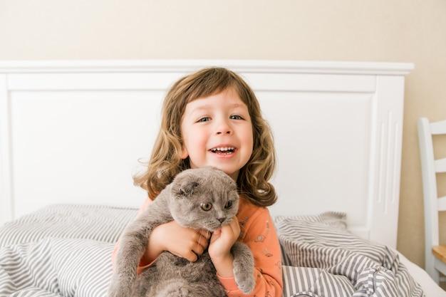 Szczęśliwa dziewczynka z kotem w łóżku mała dziewczynka uśmiecha się i bawi się ze szkockim kotem