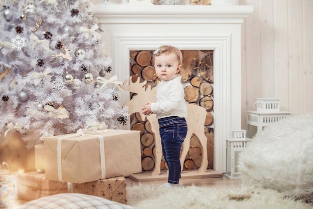 Szczęśliwa dziewczynka z prezentami w pięknych pudełkach w świątecznym wnętrzu