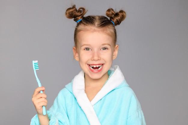 Szczęśliwa dziewczynka ze szczoteczką do zębów, zębami i uśmiechami