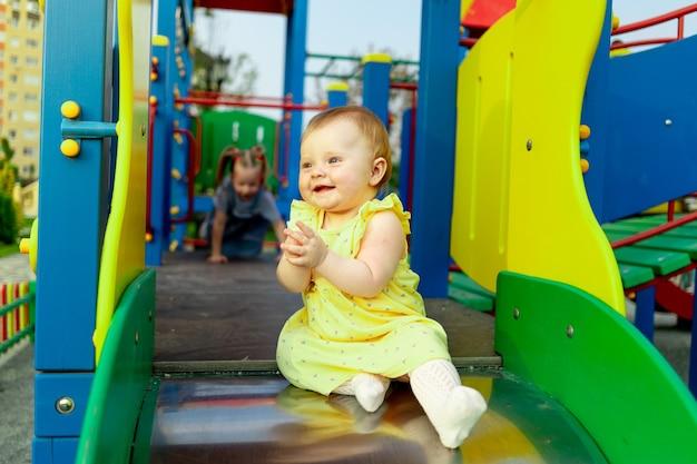 Szczęśliwa dziewczynka zjeżdża po zjeżdżalni na placu zabaw i spaceruje latem