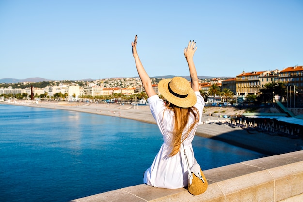 Szczęśliwa elegancka kobieta pozuje do tyłu, unosi rękę w powietrze i cieszy się niesamowitym widokiem