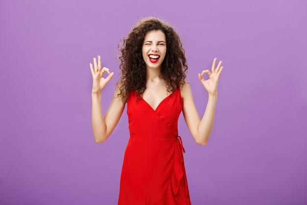 Szczęśliwa elegancka kobieta prowadząca imprezę mając pewność, że wszystko będzie w porządku, pokazując w porządku lub doskonały gest z palcami mrugając i uśmiechając się radośnie stojąc w wieczorowej czerwonej sukience noszącej luksusowy makijaż.