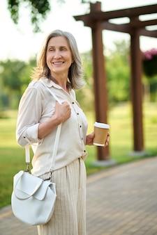 Szczęśliwa elegancka kobieta z kawą na spacerze