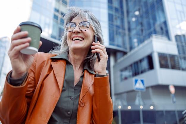Szczęśliwa emerytka z filiżanką napoju n rozmawia przez telefon komórkowy na ulicy nowoczesnego miasta