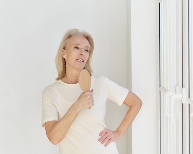 Szczęśliwa emerytowana kobieta bawi się w domu śpiewając szczotką do włosów swoją ulubioną piosenkę i patrząc w głąb