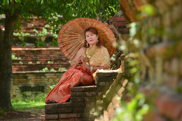 Szczęśliwa emerytowana kobieta w tradycyjnej tajskiej sukni podróżuje przy świątynią.