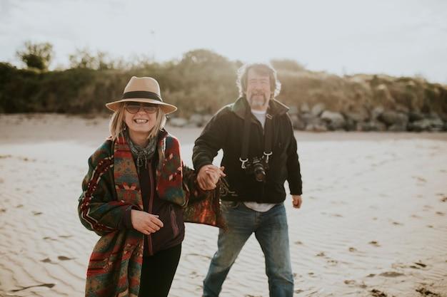 Szczęśliwa emerytowana para spaceruje po plaży?