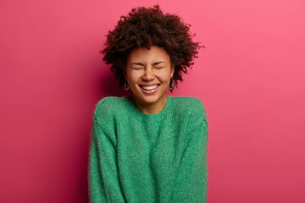 Szczęśliwa emocjonalna dziewczyna z kręconymi włosami uśmiecha się, wyraża pozytywne emocje, zamyka oczy ze śmiechu, nosi zielony sweter, czuje się optymistycznie, odizolowana na różowej ścianie, promieniuje radością.