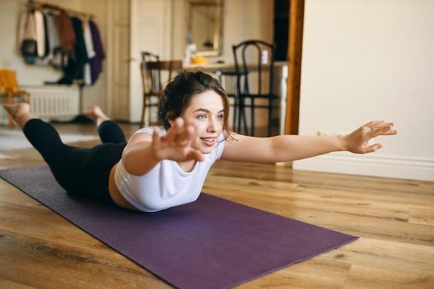 Szczęśliwa energiczna młoda kobieta robi sekwencję jogi leżąc twarzą w dół, podnosząc stopy i wyciągnięte ramiona, wyginając się do tyłu dla wzmocnienia kręgosłupa.