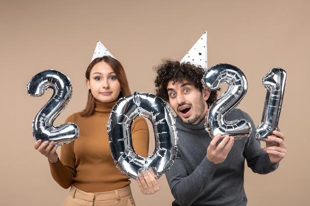 Szczęśliwa energiczna młoda para nosi kapelusz noworoczny pozuje do aparatu dziewczyna pokazuje i facet zi na szaro