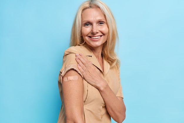 Szczęśliwa europejka o jasnych włosach pokazuje ramię z bandażem po otrzymaniu szczepionki, czuje się zadowolona, dba o swoje zdrowie, nosi brązową sukienkę odizolowaną na niebieskiej ścianie