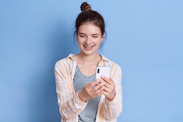 Szczęśliwa europejka ogląda śmieszne filmy na smartfonie, korzysta z bezprzewodowego internetu na urządzeniu elektronicznym, uśmiecha się delikatnie, ubiera się w zwykłe ubrania.