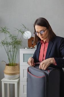 Szczęśliwa europejska milenijna kobieta biznesu pakuje walizkę do transportu drogowego dla firmy