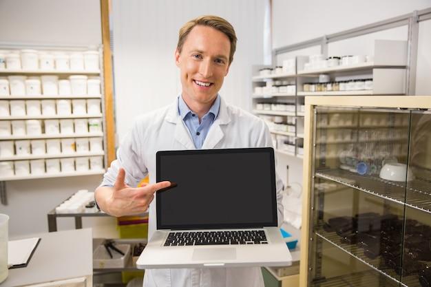 Szczęśliwa farmaceuta pokazuje laptopu ekran
