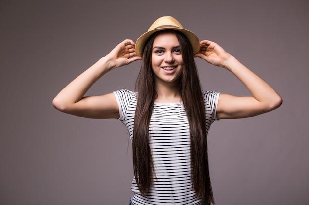 Szczęśliwa figlarna kobieta ubrana w letnią słomkową fedorę patrząc z boku na ramię