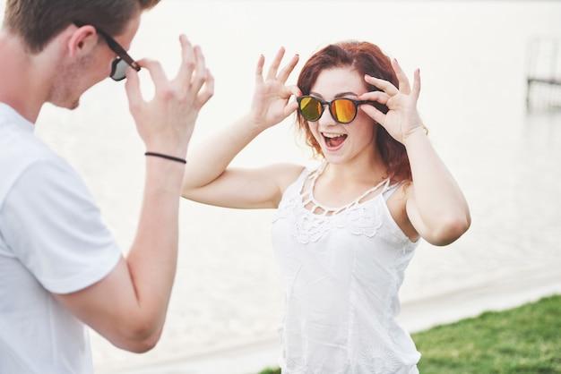 Szczęśliwa, figlarna kobieta z mężem w okularach przeciwsłonecznych