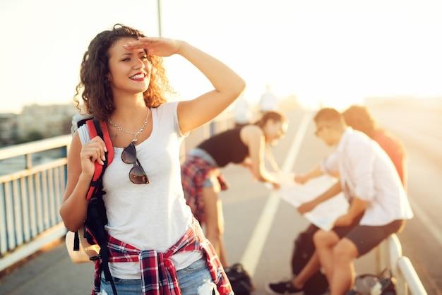 Szczęśliwa, figlarna młoda kobieta patrzy w dal, podczas gdy przyjaciele patrzą na mapę.