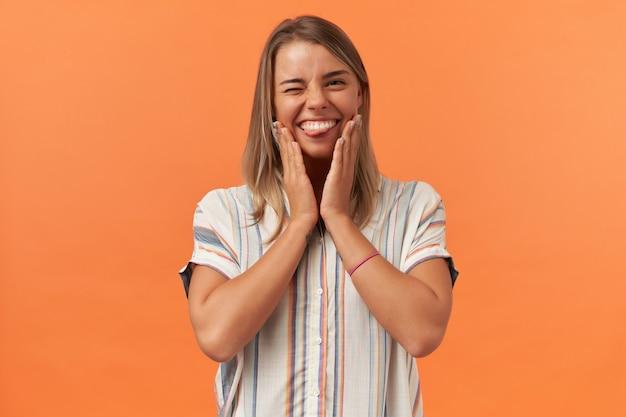 Szczęśliwa figlarna młoda kobieta w pasiastej koszuli mruga i pokazuje język odizolowany na pomarańczowej ścianie
