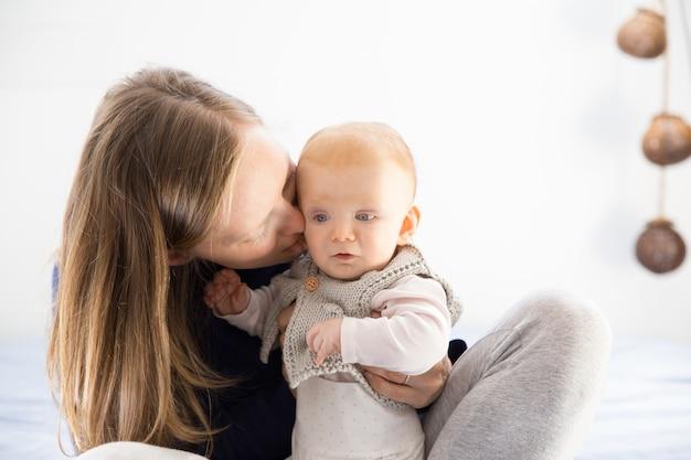 Szczęśliwa figlarna nowa mama przytulająca urocze małe dziecko