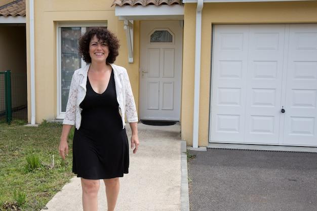 Szczęśliwa forties kobieta stoi przed nowym domem