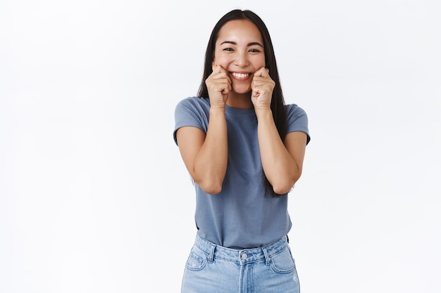 Szczęśliwa, głupia i urocza delikatna azjatycka brunetka w koszulce, ściskając policzki i ciągnąc promienny, wesoły uśmiech, mrużąc oczy, naśladując zabawne miny, stojąc radośnie na białej ścianie