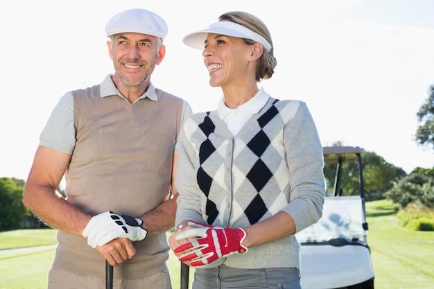 Szczęśliwa golfing para z golfowym powozikiem behind