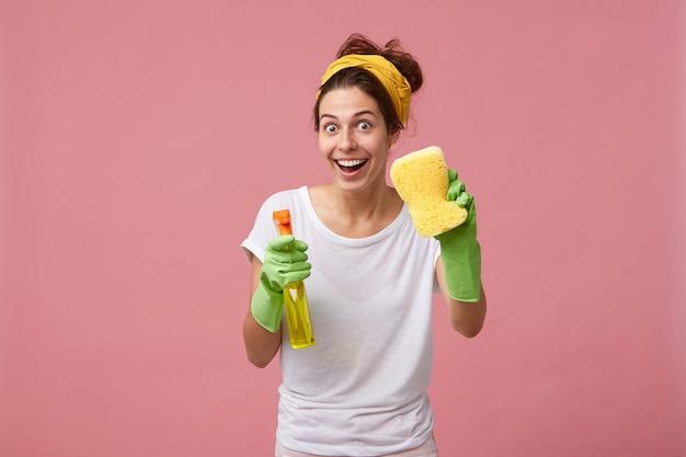 Szczęśliwa gospodyni domowa ubrana w ubranie, trzymając gąbkę i detergent, idzie do sprzątania domu o dobrym nastroju na białym tle