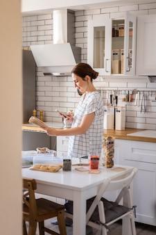 Szczęśliwa gospodyni domowa uśmiecha się pozuje i robi zdjęcia z kodem kreskowym w nowoczesnym stylu nordyckim...