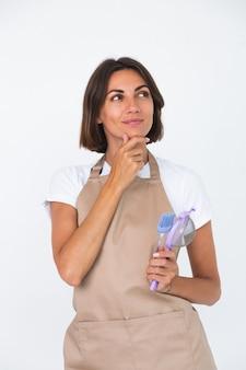 Szczęśliwa gospodyni domowa w fartuchu na białym tle przemyślana myśl o przepisie, co zrobić