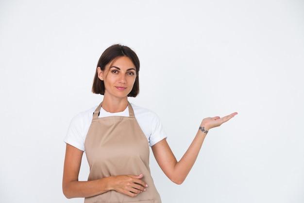 Szczęśliwa gospodyni domowa w fartuchu na białym tle trzymaj rękę w prawo z pustą przestrzenią