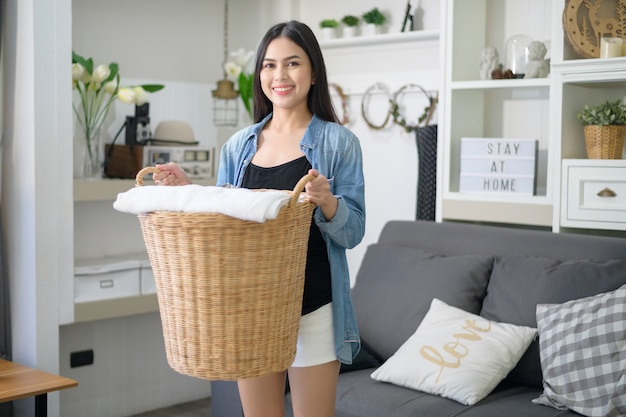 Szczęśliwa gospodyni niesie w domu wiaderko do prania.