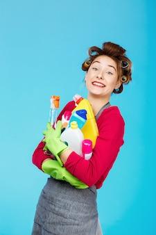Szczęśliwa gospodyni trzyma narzędzia do czyszczenia w zielonych rękawiczkach