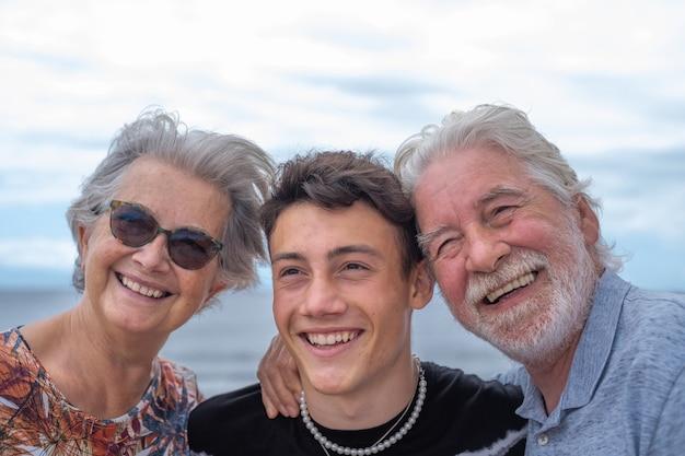 Szczęśliwa grupa dziadków z nastoletnim wnukiem siedzącym na świeżym powietrzu nad morzem, uściski i uśmiechy. przystojni ludzie bawią się razem