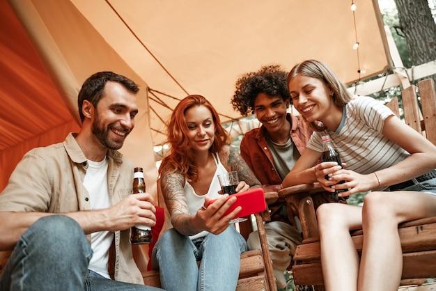 Szczęśliwa grupa młodych ludzi pijących piwo na winie za pomocą telefonów mediów społecznościowych podczas pikniku w lesie uśmiechnięci milenialsi klienci rozmawiają na zakupy online siedzą przy stole, koncepcja stylu życia technologii mobilnej
